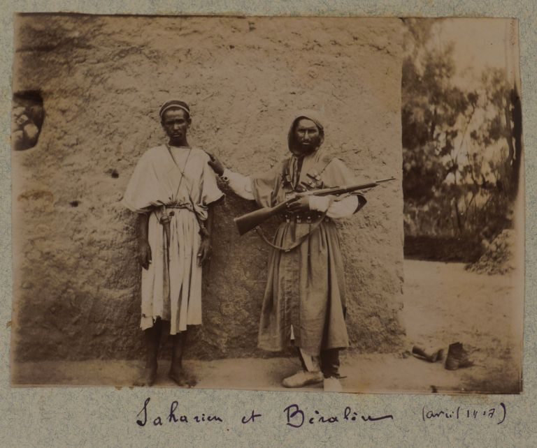 [Collection of Two Albums with 128 Original Gelatin Silver Photos Taken by a French Participant of the South-Oranese Campaign in Southwestern Algeria, Showing Towns and Military Posts (Taghit, Béni Abbès, Mazzer, Igli, Kerzaz, Tamtert, Béni Ounif, Duveyrier, Ain Sefra, Saida), Native Ksars, Military Convoys, Wounded French Military Men, Funeral and Exhumation of French Officers, Captured Berbers, Hermitage of a Catholic Hermit Charles de Foucauld, Scenes of Vaccination by Dr. Perrin, Portraits of the Local People, etc.]. MIDDLE EAST, ISLAMIC WORLD - ALGERIA.